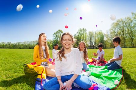 Meisje gooien kleurrijke ballen spelen met vrienden Stockfoto