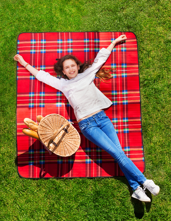 Girl relaxing on grassy meadow next to hand basket