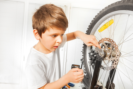 Boy repairing bike drawing up a bolt with spanner