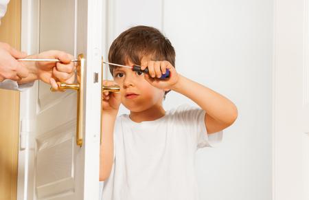 Kid boy drawing up bolt of door handle