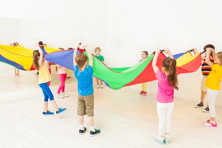 子供の円に立って、パラシュートを振って