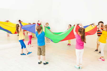 Children standing in circle and waving parachute