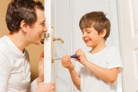 Father and  kid son repairing door handle together