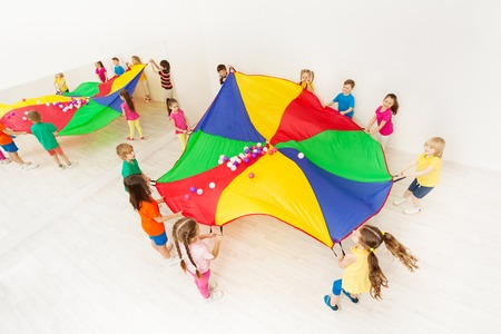 Niños jugando juegos de paracaídas en gimnasio ligero Foto de archivo - 80019981