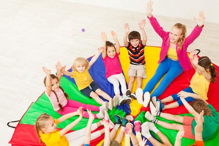Happy teacher playing circle games with children Foto de archivo