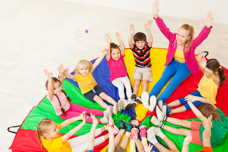 Happy teacher playing circle games with children Stock Photo