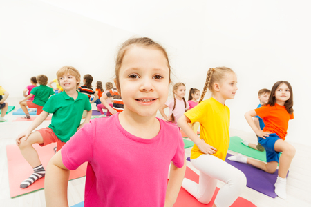 Smiling girl going in for gymnastics with friends