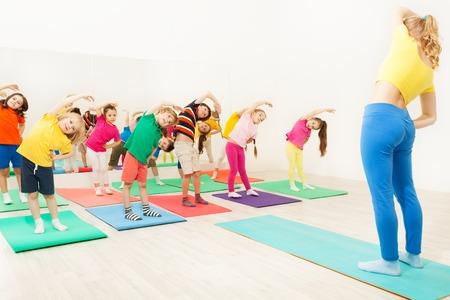 子供を横に曲げを作る体操コーチ