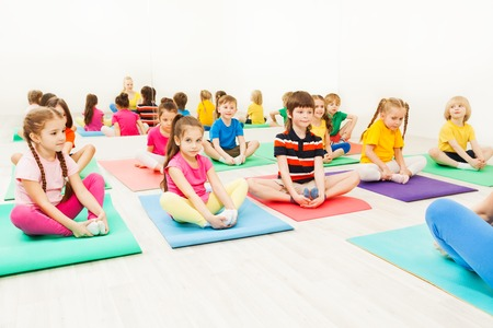 Kids doing butterfly exercise sitting on yoga mats Stockfoto