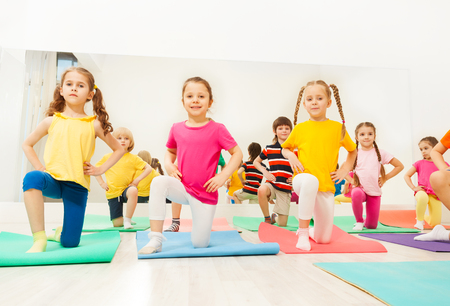Little girls standing on knee in fitness class