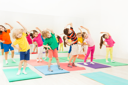 Happy kids doing side bending exercises in gym 免版税图像 - 80148807