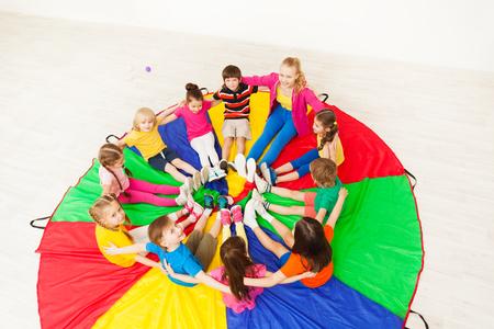 Enfants heureux et enseignant assis sur le parachute Banque d'images - 80225014