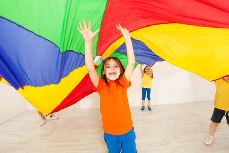 Girl hiding under parachute during sports festival Reklamní fotografie