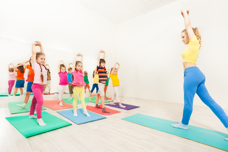 Gymnastic coach teaching kids stretching hands Stockfoto
