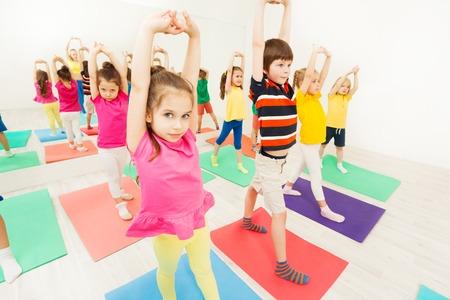 Sportieve kinderen die zich uitstrekken tijdens de gymnastiekactiviteit