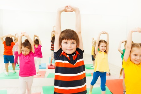체육 수업에서 스포츠 레슨 도중 손을 스트레칭하는 소년