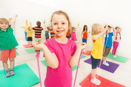 Happy kids having fun with jumping ropes in gym 스톡 콘텐츠