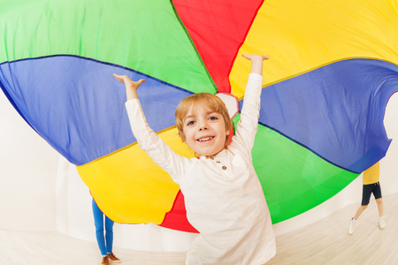 Happy boy standing under parti-colored parachute Stock Photo