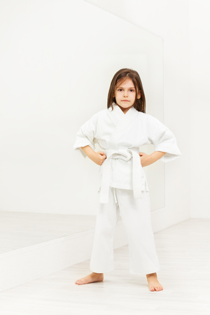 Karate girl standing with hands on hips in gym