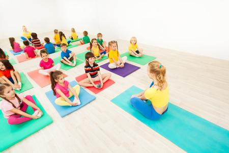 Kinderen doen vlinderrekken met vrouwelijke coach Stockfoto - 80085140
