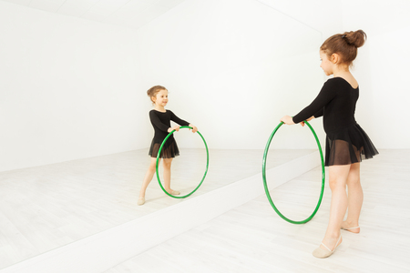 Reflection of little gymnast with dance hoop Stock Photo
