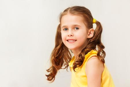 黄色のシャツがカメラ目線で微笑んでいる女の子