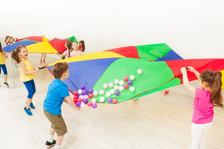 Group of children waving their arms causing the balls to pop up and off of the parachute Stockfoto