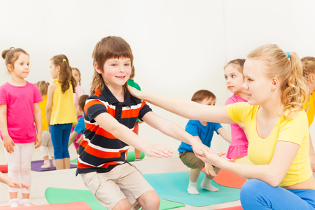 Portrait of female instructor teaching kid boy how to do squats correctly during gymnastics Stock Photo - 106036643