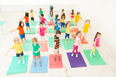 Big group of happy children doing gymnastic exercises, standing on mats in fitness class Фото со стока