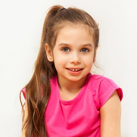 카메라를 찾고 갈색 머리 일곱 살짜리 소녀의 근접 촬영의 초상화