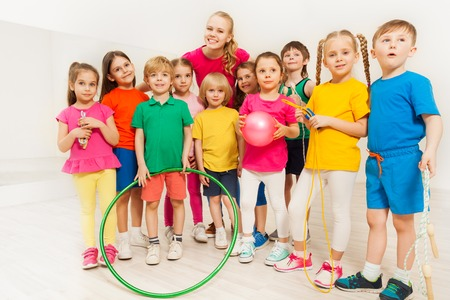 Portrait of young female sports teacher and happy kids holding sport equipment at gym