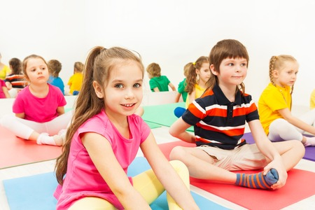 Close-up portrait of smiling six years old girl sitting in butterfly pose during kids yoga class Stockfoto
