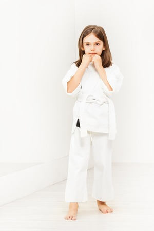 Portrait of six years old girl wearing white kimono standing in karate position in gym