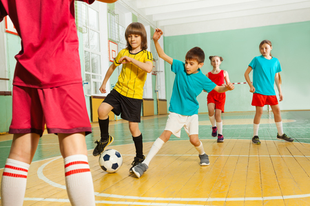 Portrait of preteen boys and girls playing football in school gymnasium Stockfoto - 106036730