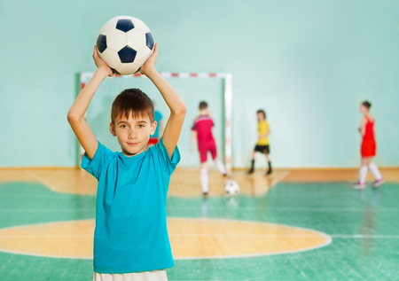 Portrait of 12 years old boy, tossing soccer ball during football match in school gymnasium Stock Photo