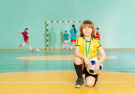 Portrait of smiling preteen boy, soccer team captain, standing on knee in futsal with ball Stock Photo