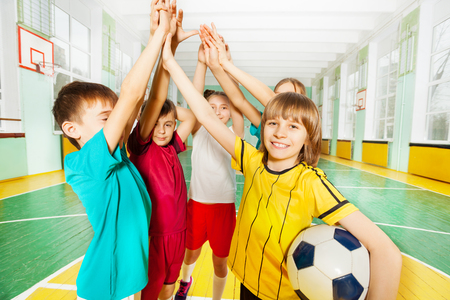 Portrait of preteen boys and girls, happy football winners, giving high five in sports hall Banco de Imagens