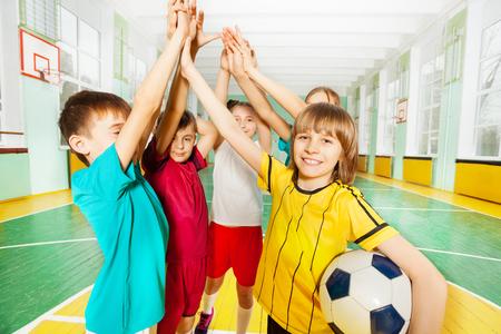 Portret van preteen jongens en meisjes, gelukkige voetbalwinnaars, die high five geven in de sporthal Stockfoto