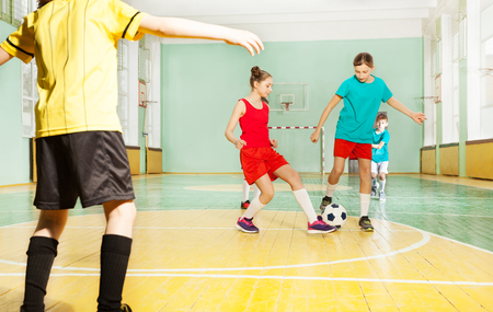 Portrait of preteen boys and girls training football in school gymnasium