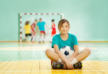 Portrait of preteen girl sitting on the floor of school gym with soccer ball Stock Photo