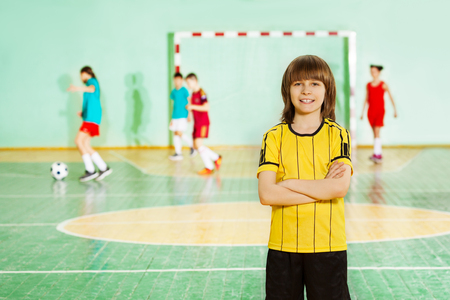 Portrait of happy 12 years old boy, football captain, standing in sports hall during the match