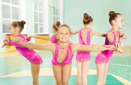 Portrait of beautiful preteen girls in pink leotards, performing rhythmic gymnastics element, forming a circle holding hands Stock Photo