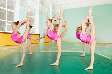 Side view portrait of 11-12 years old girls making balance, practicing rhythmic gymnastics in sports hall Standard-Bild - 106036795