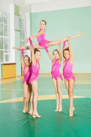 Rhythmic gymnastics group of six preteen girls showing their stretching and flexibility