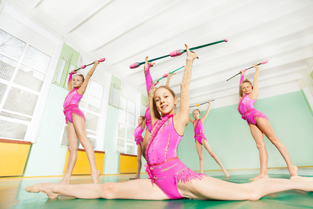 Portrait of preteen rhythmic gymnasts performing front splits and doing exercise with clubs in school sports hall