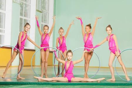 Rhythmic gymnastic team of six preteen girls performing hoop routine in school sports hall