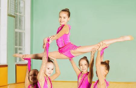 Group of beautiful preteen girls performing rhythmic gymnastics element in sports hall