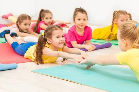 Bambini che praticano ginnastica con insegnante femminile Archivio Fotografico - 81312302