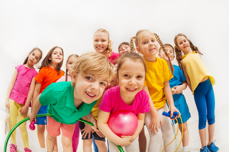 Sporty kids and gymnastics coach having fun in gym