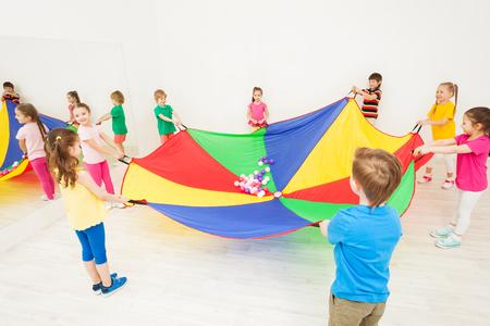 Gelukkige kinderen spelen parachutespelletjes in de sportschool Stockfoto
